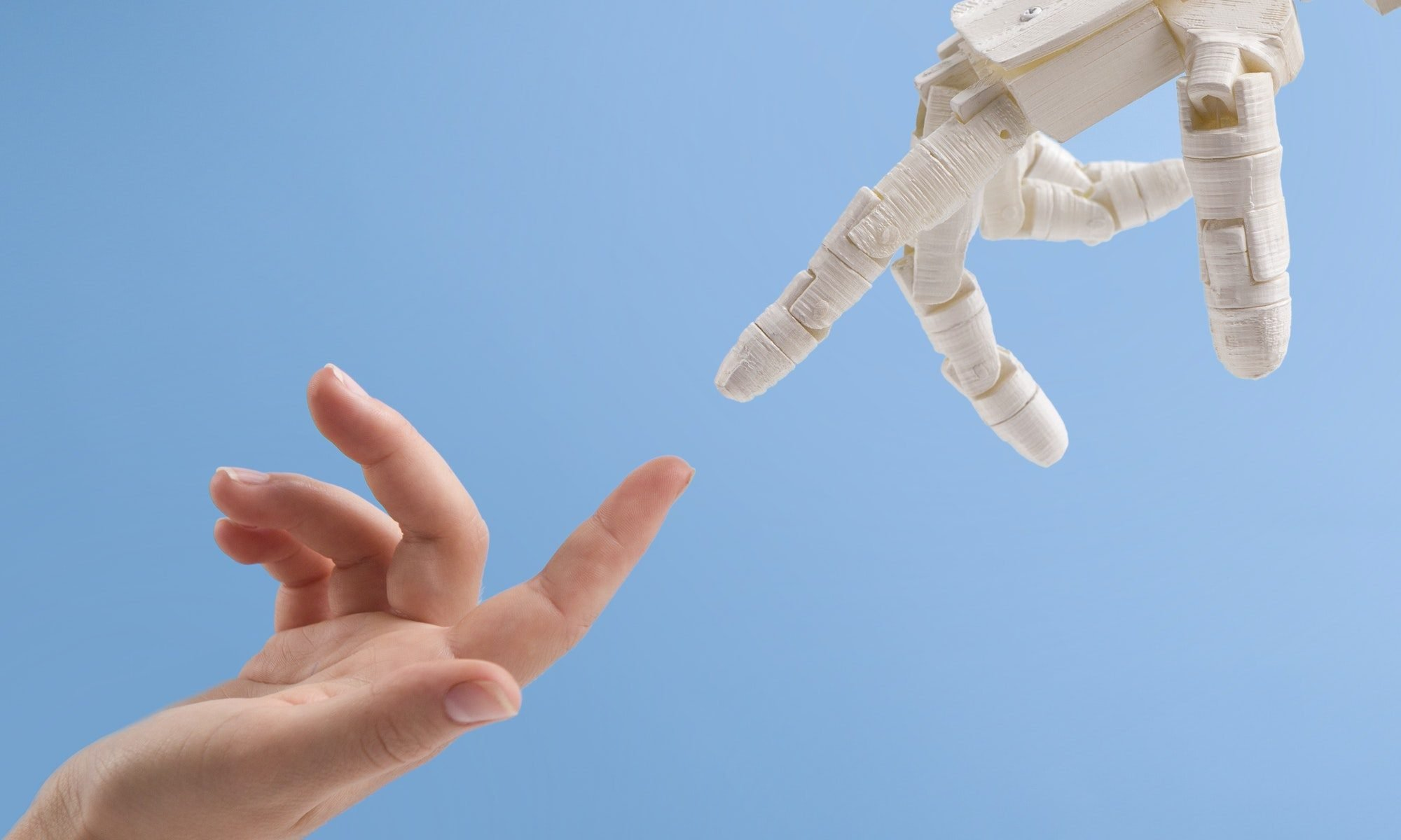 Female and robot hands reaching to each other on blue background